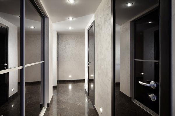 Обустраивая интерьер коридора с темными дверью и полом, обратите особое внимание на освещение