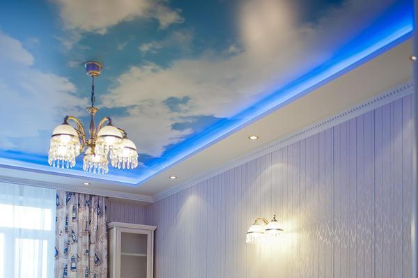 Натяжной потолок с рисунком может кардинально преобразить комнату. Например, для низкого помещения отлично подойдет мотив голубого неба