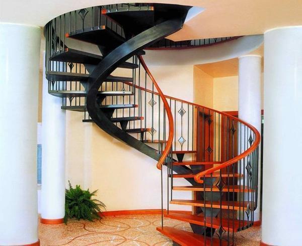 Дополнительно украсить деревянную лестницу можно красивыми кованными перилами