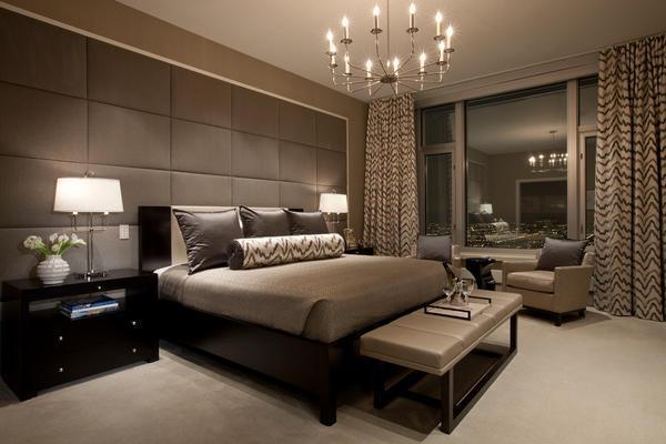 Отличным вариантом для оформления современной спальни является обивка мягкой тканью части стены, которая расположена возле кровати