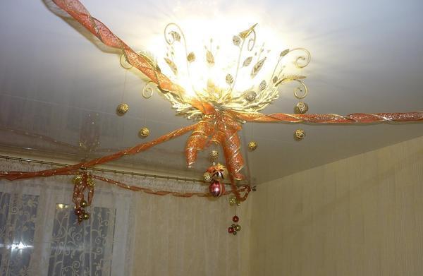 Чтобы не тратить много финансовых средств на покупку дорогостоящих украшений, можно приобрести широкую подарочную ленту и с помощью ее украсить потолок