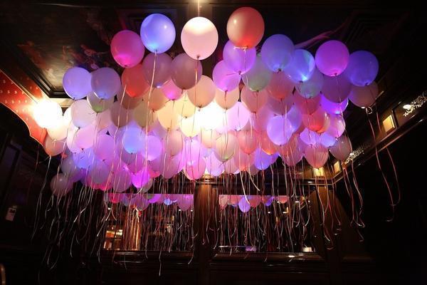 Креативно украсить гостиную можно светящимися шарами с гелием