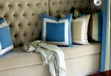 pared-tapizada-en-terciopelo-verde-seco-con-capitone-y-banco-con-cojines-azul-y-verde