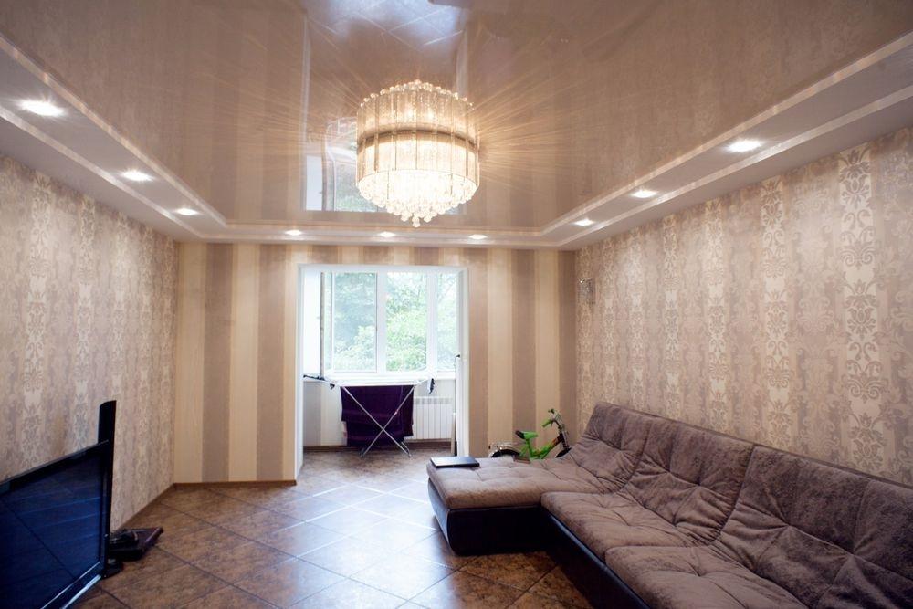Натяжной потолок в зале с люстрой и точечными светильниками фото