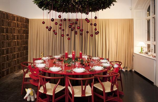 Неординарным решением является применение новогодних игрушек, свисающих с декоративного растения над праздничным столом