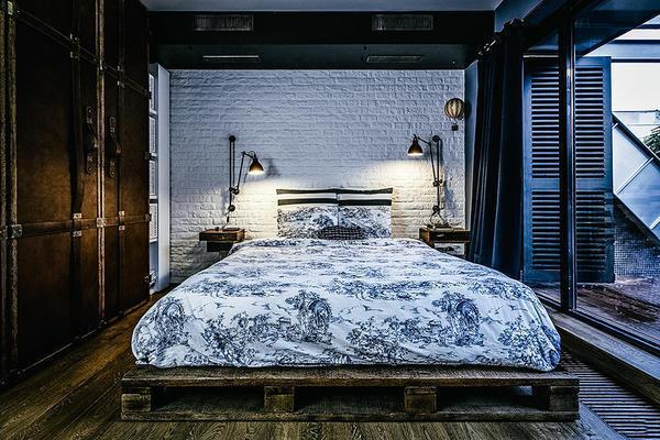 Кровать в спальне лофт должна быть большого размера и обязательно на низеньких ножках