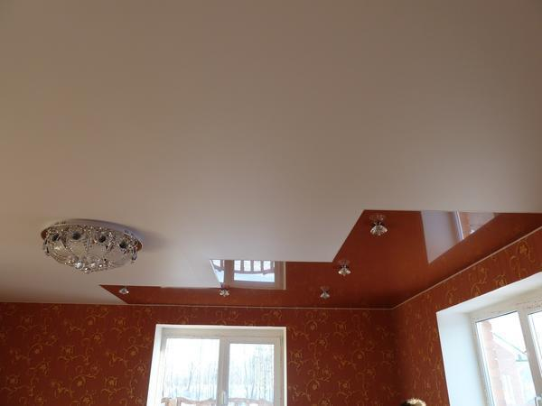 Чтобы матовый потолок не казался монотонным, его можно разнообразить путем поклейки глянцевого покрытия в определенном углу или по периметру