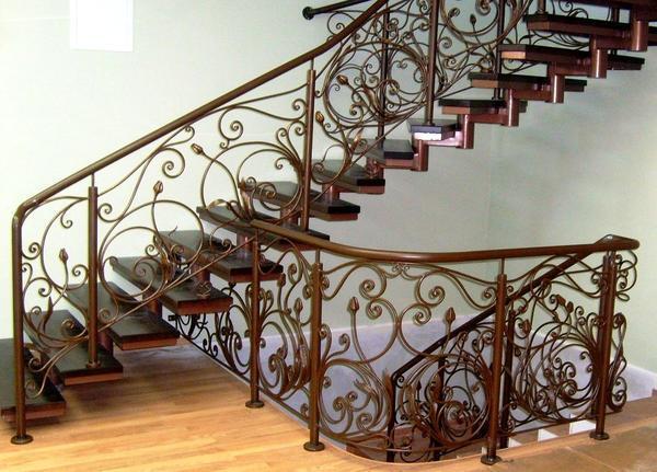 Украсить лестницу на металлическом каркасе можно с помощью перил с кованными элементами