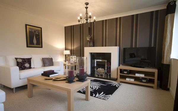 Для гостиной хорошим вариантом является акцентирование на области, где размещен телевизор или камин