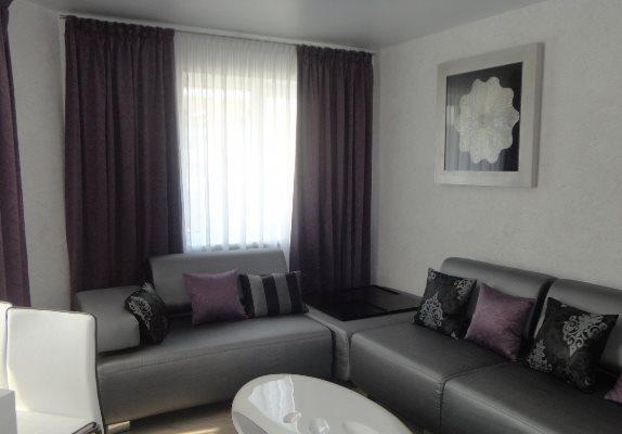 Красивый серый диван прекрасно впишется в интерьер любой гостиной